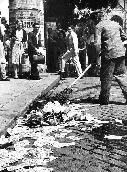 A Hungarian man sweeps paper money out of the gutter